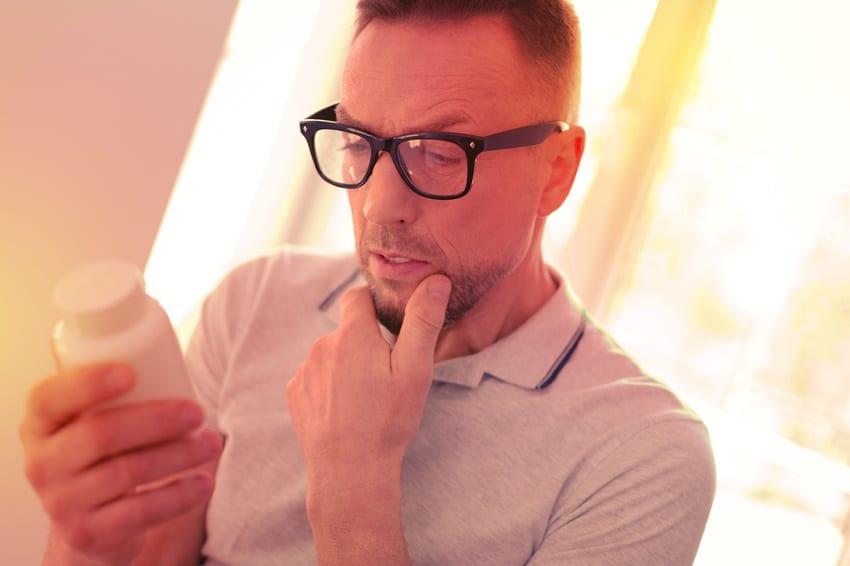 Confused man looking at vitamins