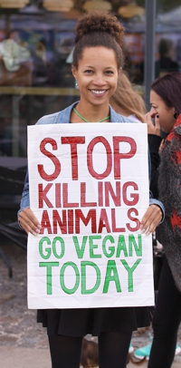 Vegan holding sign in protest of killing animals