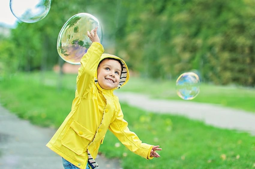 Child playing with bubbles outdoors