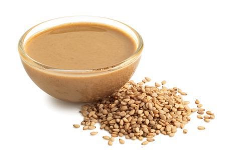 Tahini in a glass bowl with sesame seeds