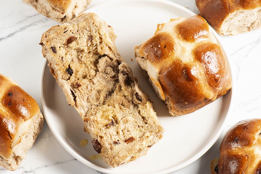 Hot crossed buns on a plate sliced open
